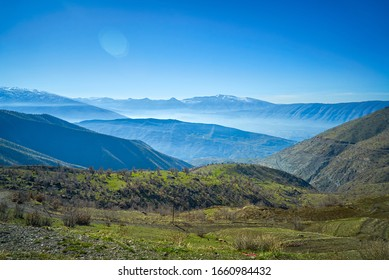 a view of mountains covered with snow in the fall session in  the north of Iraq Kurdistan Region with green landscape and trees in the foreground
