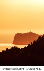 View from the mountains to the famous balearic island Sa Dragonera in beautiful golden sunset glow with the lighthouse silhouette. Sa Dragonera, Mallorca, Spain