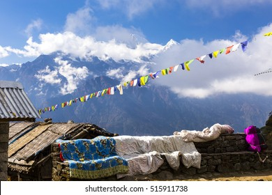 View of Mountains with high snowy peaks and blue sky with traditional Nepalese flags garland and roofs of primitive masonry buildings of trekking lodge on foreground
