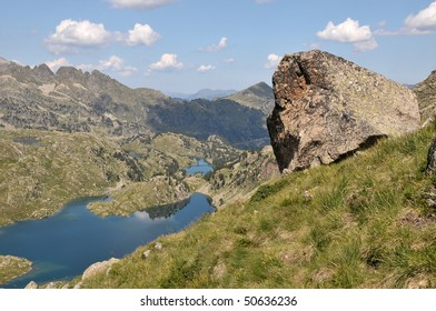View of mountains and lakes with a big rock in foreground.