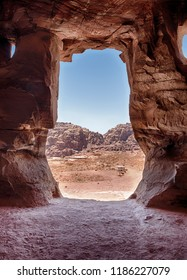 A view of the mountains of Petra through the stone entrance of one of the Royal Tombs.