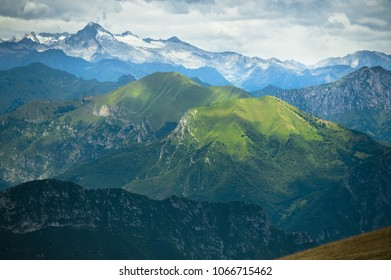 View of the mountains taken from the Monte Baldo, showing peaks situated between Garda and Ledro lakes, Norhern Italy. The sunlight reaches the Green hills from behing clouds.