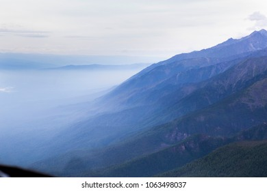 """View of the mountains of the Tunkinsky National Park in the Republic of Buryatia of the Russian Federation from the cockpit of the helicopter. The name of the mountain range - """"Eastern Sayans""""."""