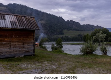 a view of the mountains, a wooden house, a bonfire with smoke