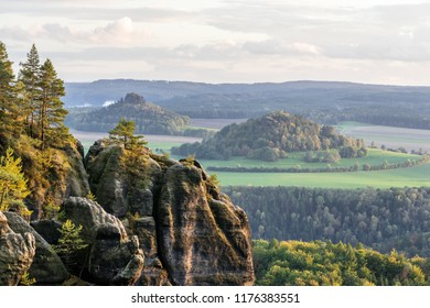 "View to the mountains ""Zirkelstein"" and ""Kaiserkrone"", in the foreground a rock formation with trees in autumn color, light haze - Location: Germany, Saxony, Elbe Sandstone Mountains, ""Schrammsteine"""