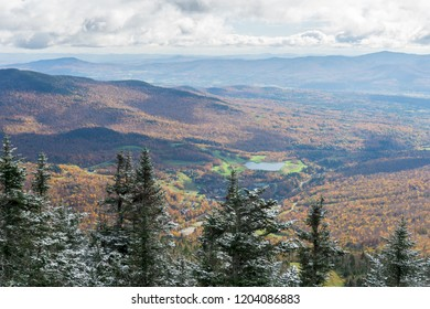 View from Mountaintop with Snow Overlooking Valley of Peak Fall Colors and Small Lake