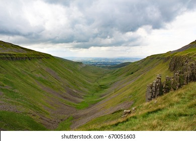 View of mouth of High Cup Nick a U-shaped valley in the northern Pennines in Cumbria, England, with the grey-blue dolerite crags seen on the right hand side