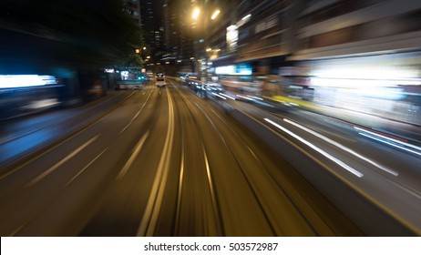 View from moving double-decker tram in Hong Kong. Night street with transport and rails