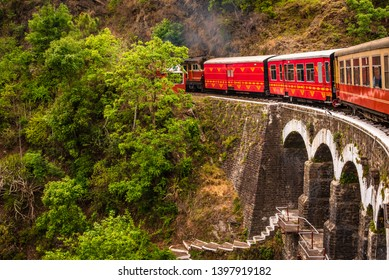 View from moving train on arch bridge over mountain slopes, beautiful view, one side mountain, one side valley. Toy train from Shimla to Kalka in Himachal Pradesh, India