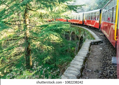 View from moving train on mountain slopes, beautiful view, one side mountain, one side valley. Toy train from Shimla to Kalka in Himachal Pradesh, India