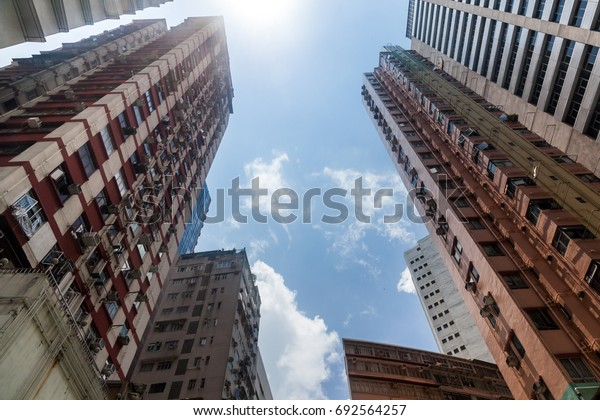 View of multistory residential complex with apartments in metropolis center of Hong Kong. A perspective view from the bottom up