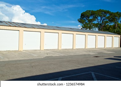 View of multi-unit or multi-bay garage type storage building abandoned in Florida in bright sunshine with large tree and clouds and broken driveway. Metal roof is old, damaged and rusted.