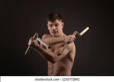 View of a muscled man  in  single combat weapon pose with nunchaku  on a black background in studio