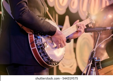 View of musician playing banjo in concert at night. Movement. Shallow depth of field.