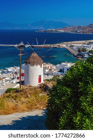 View of Mykonos windmill and old port with ships and boats