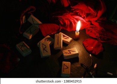View of the mystical composition of wooden runes around the petals of red roses, a candle burns next to it and the burnt matches lie. Blur dark background