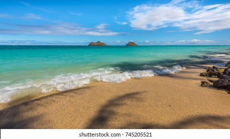 View of Na Mokulea (Mokulea Islands) from the shores of Lanikai Beach, in Kailua, Hawaii, Oahu - see the palm tree leaf shadows on the sand, as calm waves roll in on a sunny afternoon