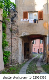 """View of a narrow, sinuous alley (""""carruggio"""") under an arched building with a clothes line out of a window in the old town, Sestri Levante, Genoa, Liguria, Italy"""