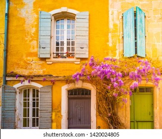 View of a narrow street with gorgeous purple wisteria plant in the historical center of Arles, France. Beautiful background picture of the old french town.