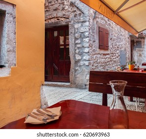 View of narrow street with walls of coarse stone, wooden door and close window shutters in old marine town with summer cafe under awning and empty wine carafe on table in Croatia