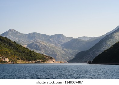 """View of the narrowest passage in Boka Kotorska Bay called """"Chain"""". Summer seascape in Montenegro. Sunlit mountains and sea."""