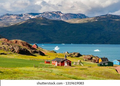 The view of Narsarsuaq in Greenland and the bay with icebergs. In the background mountains and blue sky with some clouds.