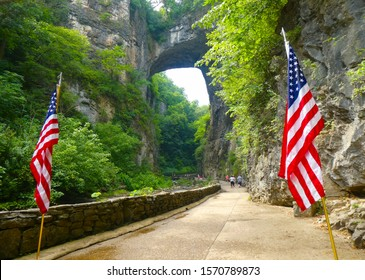 View of Natural Bridge in Virginia on the 4th of July with American flags in the foreground.