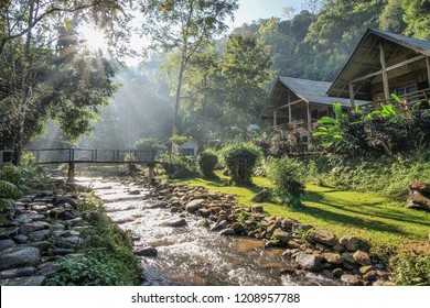 view nature of water flowing on the arch rocks around with green forest, huts and sun rays background, Ban Mae Kampong Royal Project, Mae On District, Chiang Mai, northern Thailand.