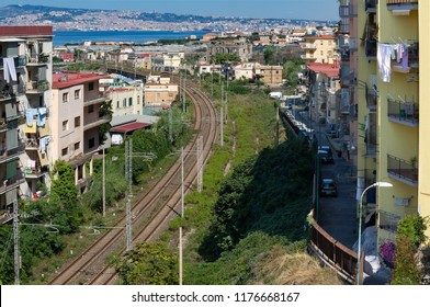 View of a neighborhood with buildings and railway of Torre del Greco. The sea and the city of Naples is reflecting at the horizon - Italy