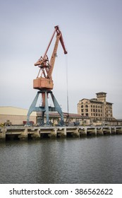 view of Nervion river and industrial port area with crane and factory at the entrance to Bilbao, on the surroundings of Erandio and Sestao villages