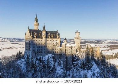 View of Neuschwanstein Castle from  Queen Mary's Bridge surrounded by trees and snow