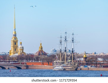 View of the Neva embankment in St. Petersburg with the spire of the Petropavlovsk fortress, sailing ship and golden domes of churches