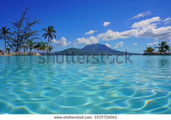 View of the Nevis Peak volcano from a swimming pool in Christopher Harbour, St Kitts