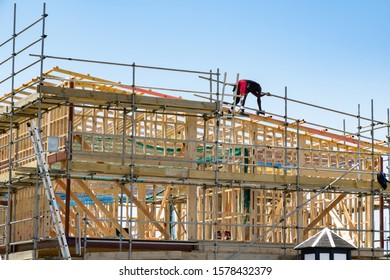 View of new home construction site with wooden frame and worker on the roof