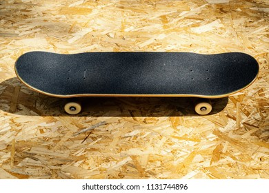 view of a new skateboard with white wheels on a wooden background in a skatepark in the summer