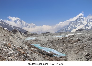 View of Ngozumpa glacier covered with stones in Himalayas in Nepal at an altitude of about 5000 meters. The glacier is surrounded by mountains, and lakes of melted ice are visible on its surface.