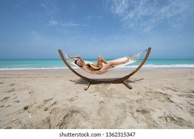 view of nice girls swinging in hummock on sea beach