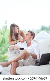 view of nice young couple is sitting on sofa in summer house