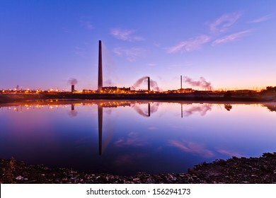 View of nickel plant with big and tall chimney during sunrise