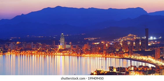 View the night city with lights reflected in sea at sunset (View Benidorm, Spain)