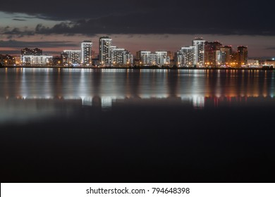 view of night city reflecting in the water