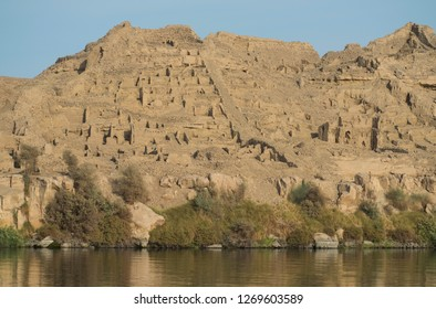 View from the Nile River of ancient egyptian town ruins on mountainside in Aswan Egypt