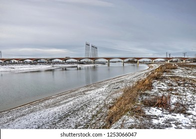 View from the north bank of the new channel of the river Waal near Nijmegen, The Netherlands with city bridge De Oversteek (The Crossing) in the background, on a cold day in winter