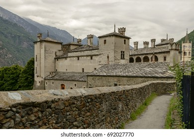 view from north west of the ancient castle with walk surrounded by stone walls in foreground, shot under bright cloudy sky at Issogne, Aosta valley,  Italy
