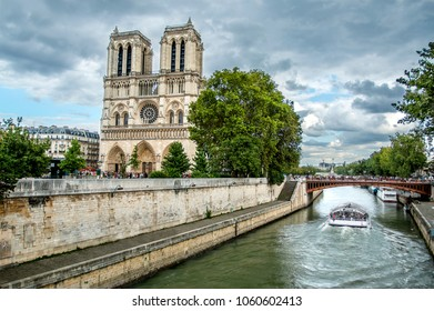 View of Notre-Dame Cathedral on city Sena river bank with cloudy sky and green trees among