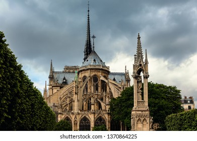 View of Notre-Dame de Paris Cathedral under cloudy sky.
