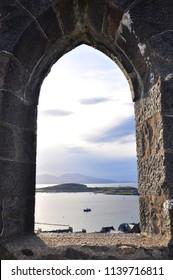 A view of Oban Bay through an arch of McCaig's Tower. Oban, Scotland