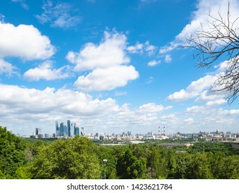 view from observation deck on Sparrow Hills (Vorobyovy Gory) - white cimulus clouds in blue sky over Moscow city in summer day