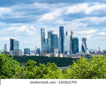 view from observation deck on Sparrow Hills (Vorobyovy Gory) - skyscrapers of Moscow-city district under dark blue clouds