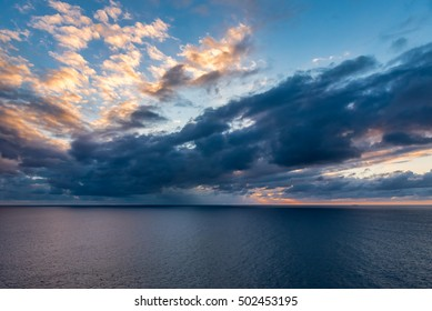 View of the ocean horizon with the sun setting and reflection on the clouds with storm clouds below.
